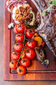 Tomate grelhado de bife tomahawk com purê de batata, queijo assado de espinafre e molho de molho.