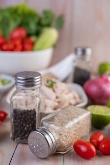 Tomate, juntamente com um pote de sementes de gergelim, colocado em uma mesa de madeira