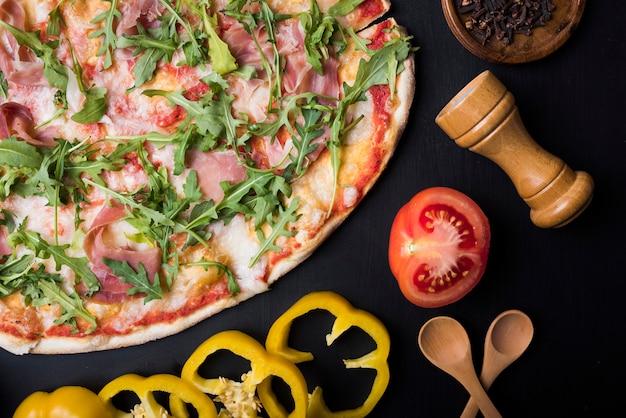 Tomate meio cortado; fatias de pimentão amarelo; colher de pau e peppermill perto de uma deliciosa pizza italiana