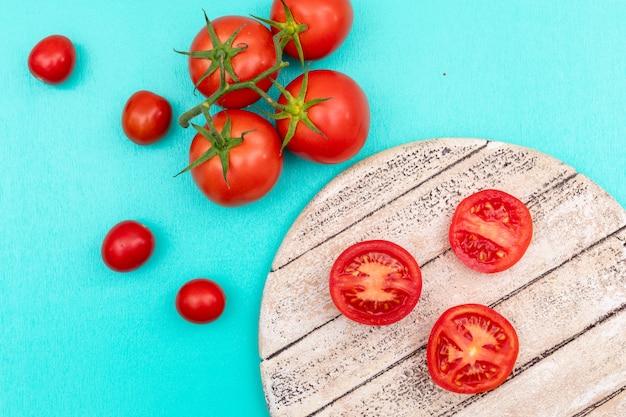 Tomate no ramo de tábua de madeira de tomate cereja na superfície azul vista superior