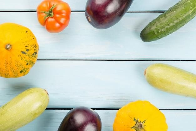 Tomate, pepino, abóboras, berinjela e medula na mesa de madeira azul com fundo copyspace