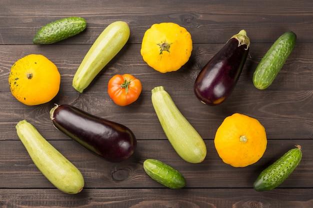 Tomate, pepino, abóboras, berinjela e medula na mesa de madeira escura.