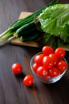 Tomate, pepino, salada verde e cebola. legumes caseiros do jardim ou jardim.