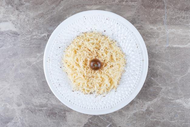 Tomate pequeno e macarrão no prato, na superfície de mármore.
