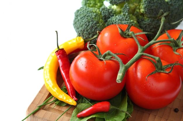 Tomate, pimenta e brócolis em uma placa de madeira
