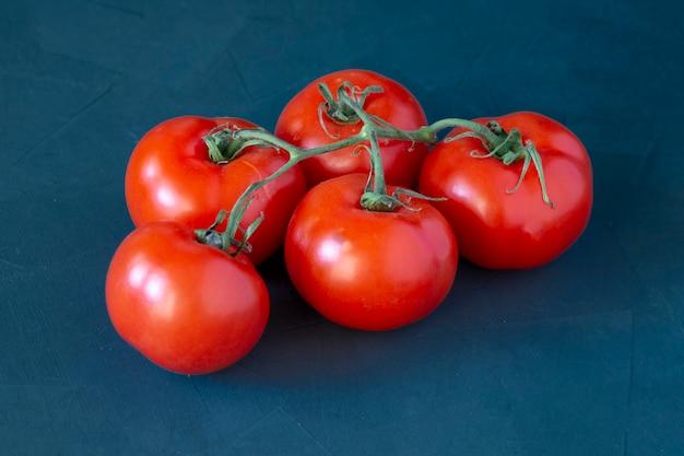 Tomate vermelho em um galho em uma mesa. comida saudável rica em vitaminas e antioxidantes comida vegetariana