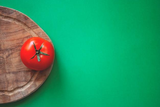 Tomate vermelho em uma tábua de madeira sobre uma superfície verde. tirado por uma câmera de cima.