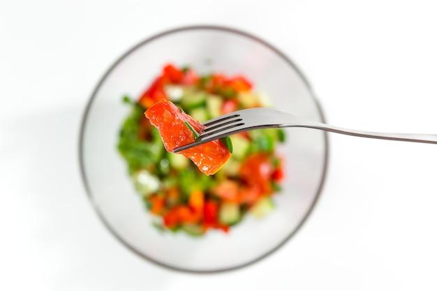 Tomate vermelho fresco em um garfo. salada fresca com vegetais, tomates, pepinos, alface, folhas de salada na vista superior de fundo branco. conceito de alimentação e dieta saudável. comida vegetariana