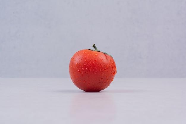 Tomate vermelho fresco na superfície branca