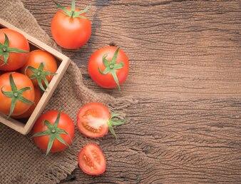 Tomate vermelho fresco no fundo de madeira, vista superior