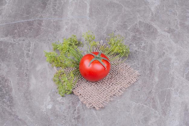 Tomate vermelho único com ervas em um pedaço de serapilheira.