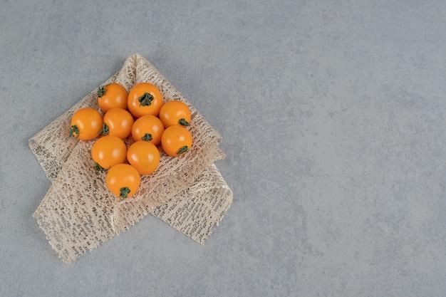 Tomates amarelos isolados na superfície da pedra