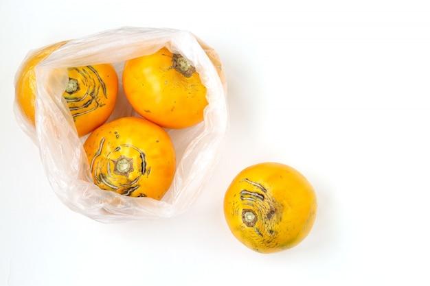 Tomates amarelos orgânicos feios em saco plástico, a imagem mostra os danos do uso de sacos de armazenamento de alimentos artificiais