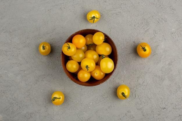 Tomates amarelos, uma vista superior da vitamina madura fresca, rica em pote redondo marrom na luz