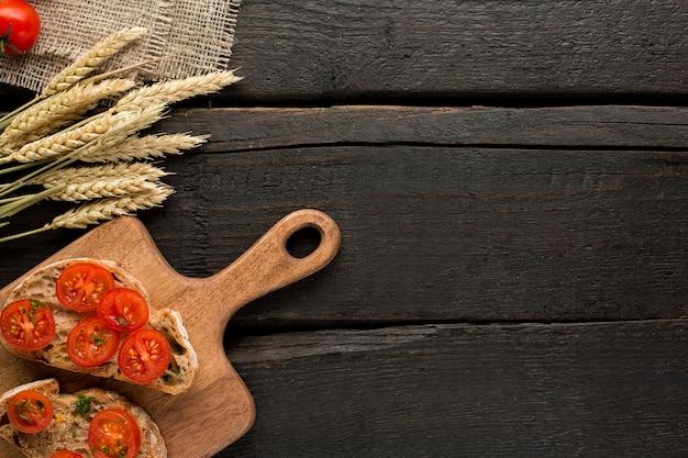 Tomates brindes e pão em uma placa