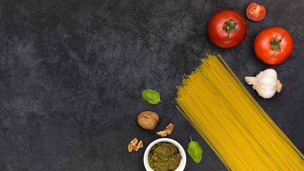 Tomates; bulbo de alho; manjericão; nozes; molho e espaguete no pano de fundo texturizado preto
