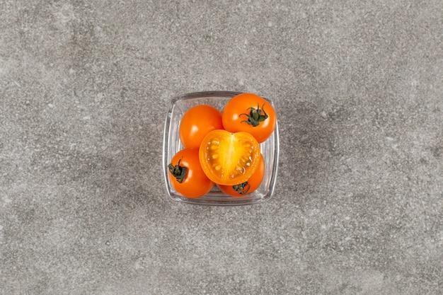 Tomates cereja amarelos frescos em uma tigela de vidro.