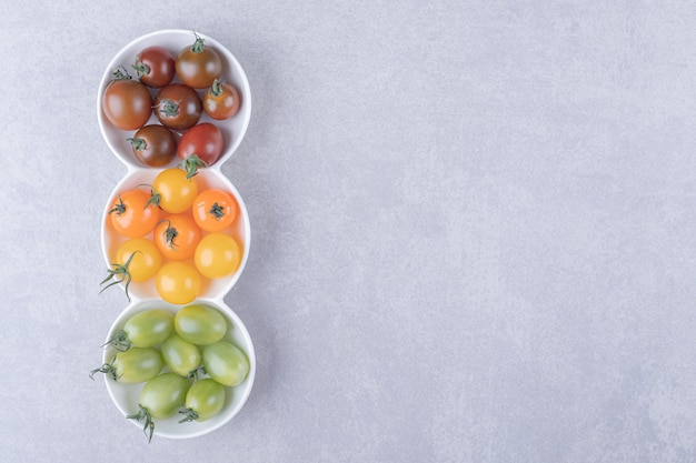 Tomates cereja coloridos em tigelas brancas.