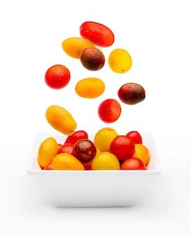 Tomates cereja coloridos (vermelho, granada e amarelo), frescos e crus caindo em um negrito. com gotas de água isoladas em um fundo branco