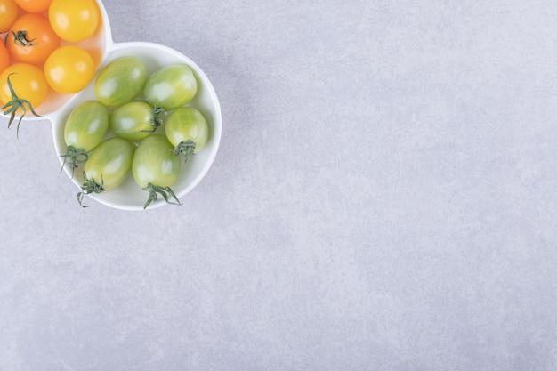 Tomates cereja de cor verde e laranja em tigelas brancas.