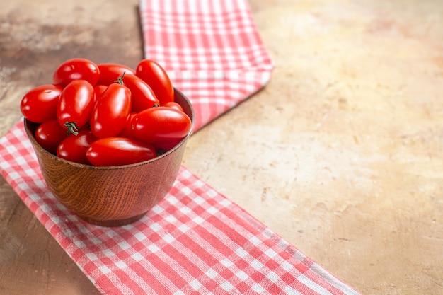 Tomates cereja de vista frontal em uma tigela de madeira, uma toalha de cozinha em um espaço livre de fundo âmbar