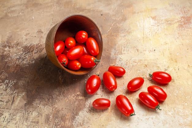 Tomates cereja de vista frontal espalhados da tigela no espaço livre âmbar