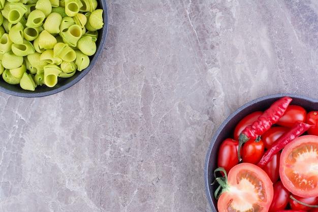 Tomates cereja e pimentões vermelhos em uma panela preta com massas verdes ao redor.