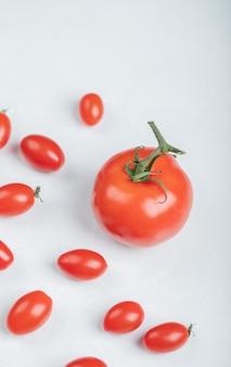Tomates cereja em torno do tomate normal. foto de alta qualidade