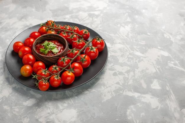 Tomates cereja frescos de vista frontal dentro do prato com molho de tomate na superfície branca salada de legumes refeição saudável