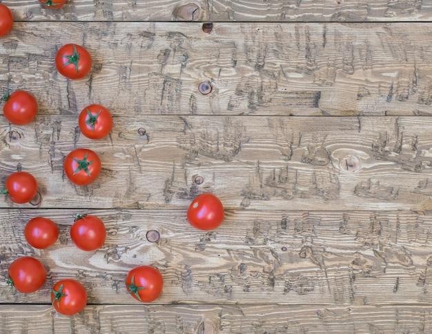 Tomates cereja frescos espalhados sobre um fundo de mesa rústica