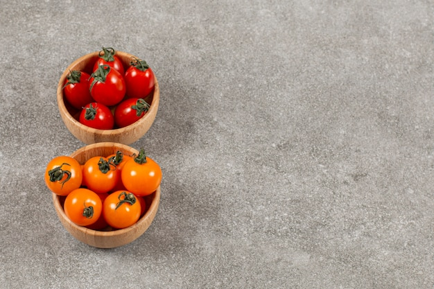 Tomates cereja orgânicos em duas tigela separadas vermelhas e amarelas.