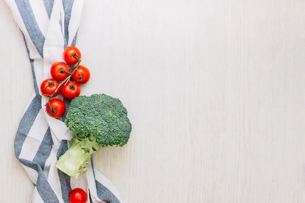 Tomates-cereja vermelhas e brócolis sobre a toalha contra a superfície de madeira