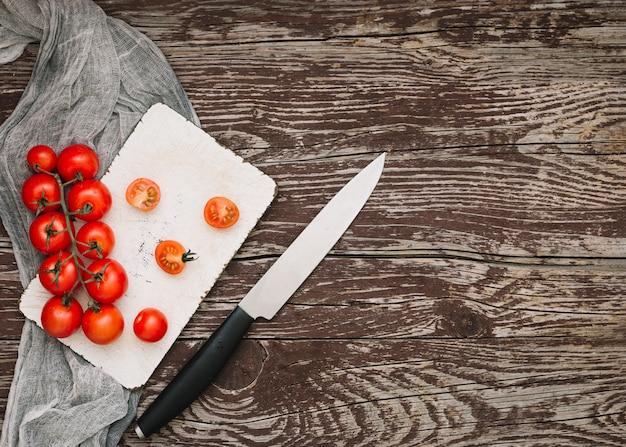 Tomates-cereja vermelhas na tábua de cortar com a faca sobre a mesa de madeira