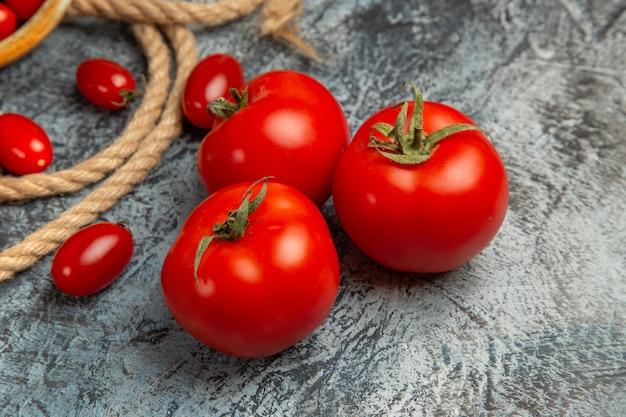 Tomates cereja vermelhos de vista frontal com cordas