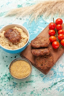 Tomates cereja vermelhos de vista frontal com costeletas de carne na superfície azul refeição de carne de vegetais