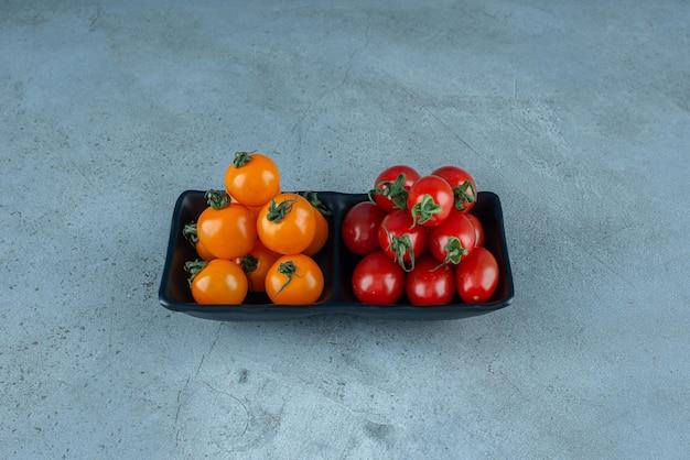 Tomates cereja vermelhos e amarelos em uma travessa preta.