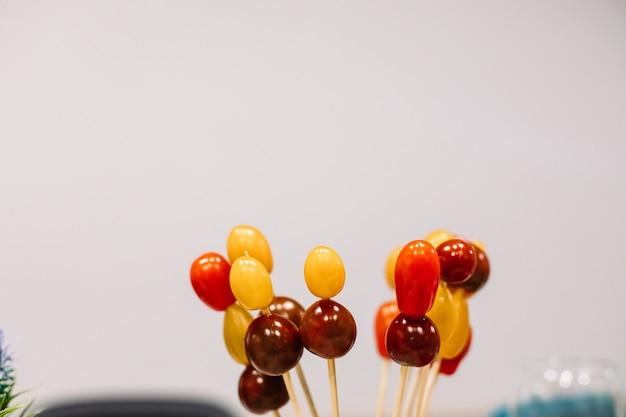 Tomates cereja vermelhos e amarelos sortidos em varas de madeira em fundo branco. copie o espaço. conceito de lanche e comida.
