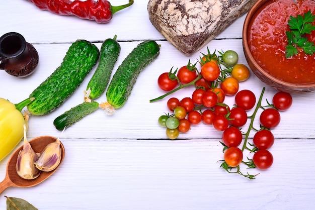 Tomates-cereja vermelhos e um prato de sopa fria de gaspacho