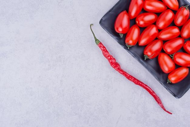 Tomates cereja vermelhos em uma bandeja preta com pimenta ao redor.