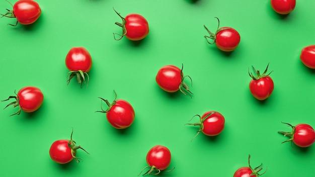 Tomates cereja vermelhos frescos em fundo verde, vista superior