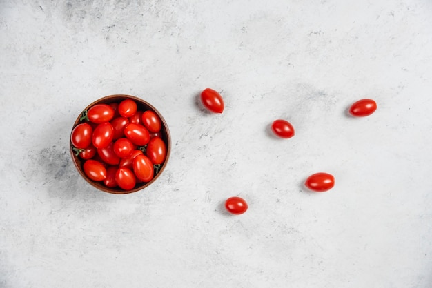 Tomates cereja vermelhos frescos em uma tigela de madeira