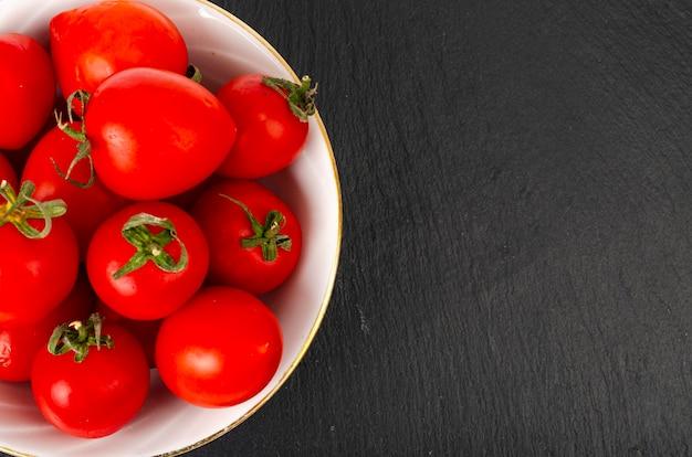 Tomates cereja vermelhos pequenos maduros em saladeira branca.