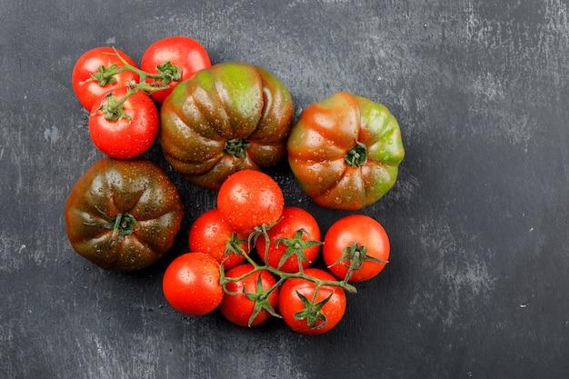 Tomates chuvosos em uma parede cinza suja. vista do topo.