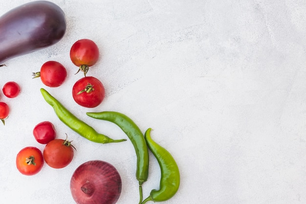 Tomates colhidos; pimentos verdes; cebola e berinjela em fundo branco