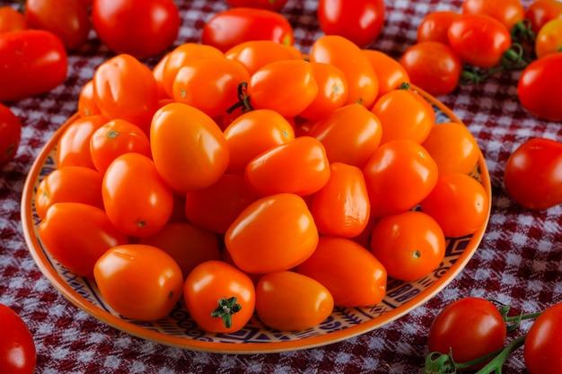 Tomates coloridos em um prato no pano de piquenique, vista de alto ângulo.