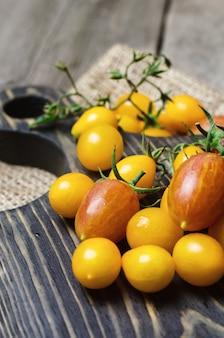Tomates de cereja amarelos e vermelhos na tábua de madeira.