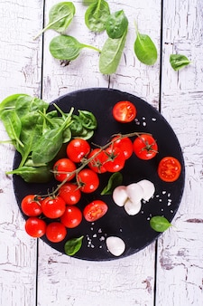 Tomates de cereja frescos, mussarela e espinafres verdes no fundo de madeira.