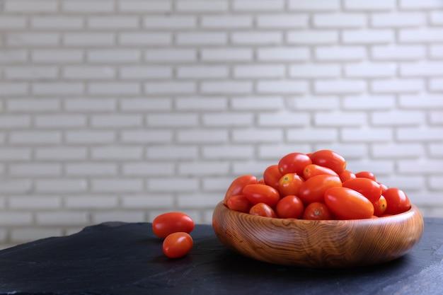 Tomates de cereja frescos na bacia de madeira com parede branca.
