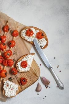 Tomates de cereja grelhados em espetos, no papel de cozimento. bruschetta italiana com tomate e queijo