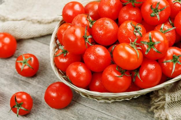 Tomates de cereja maduros e suculentos com gotas da umidade em uma cesta de vime. mesa de madeira velha, em torno da tela de serapilheira